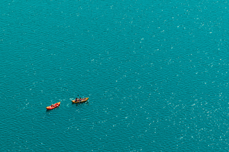 Unrecognizable people enjoying hot summer afternoon in boats on lake Bled, aerial view of leisure and recreational activity for holiday vacation in Slovenia Stock Photo