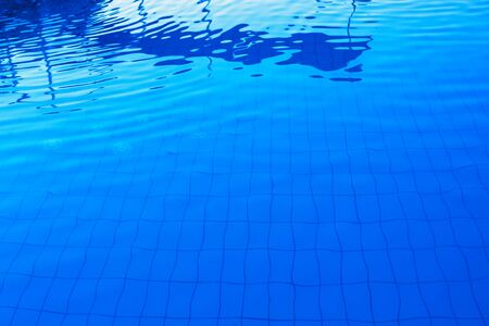 Blue outdoor swimming poolside water surface as abstract background for summer holiday vacation themes