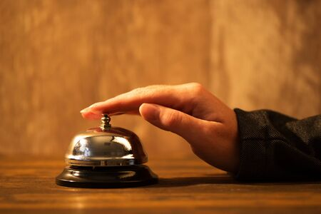 Businesswoman ringing hotel reception bell, warm retro toned image with selective focus