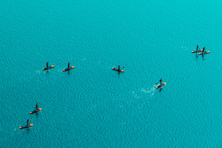 Aerial view of unrecognizable group of people stand up paddle boarding on water surface for sport, fun, leisure or recreational pursuit. Enjoying summer SUP activity for holiday vacation. Stock Photo