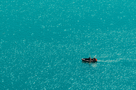Unrecognizable couple enjoying summer afternoon in boat on lake Bled, aerial view of leisure and recreational activity for holiday vacation in Slovenia