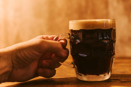 real ale: Man drinking dark beer in british dimpled glass pint mug on bar table