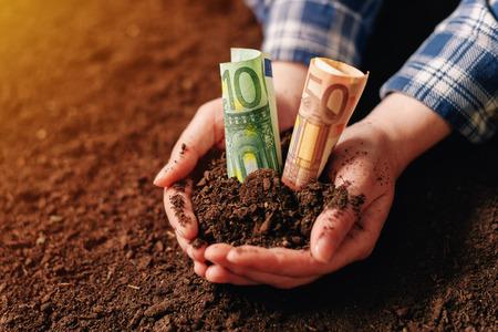 Handen met vruchtbare grond en euro geld bankbiljetten, vrouwelijke boer handvol gecultiveerd land dat winst en een vast inkomen maakt van duurzame landbouwactiviteiten zoals organische groei van gewassen Stockfoto