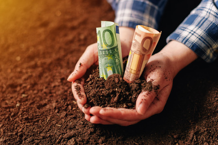 Hands with fertile soil and euro money banknotes, female farmer handful of cultivated land that makes profit and steady income from sustainable agricultural activity like organic growth of crops