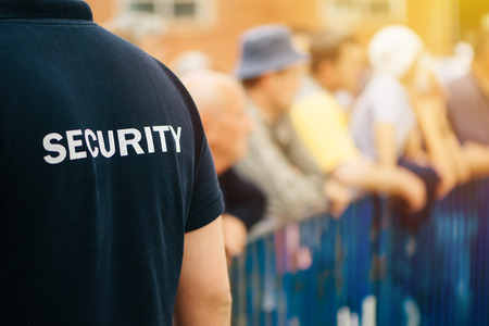 Member of security guard team working on public event, unrecognizable male person from behind