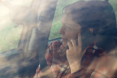 mobile telephone: Smiling woman talking on mobile phone in car, satisfied adult female person during telephone conversation