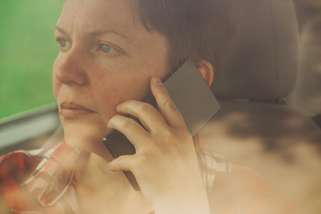mobile telephone: Worried woman talking on mobile phone in car, concerned adult caucasian female person during telephone conversation