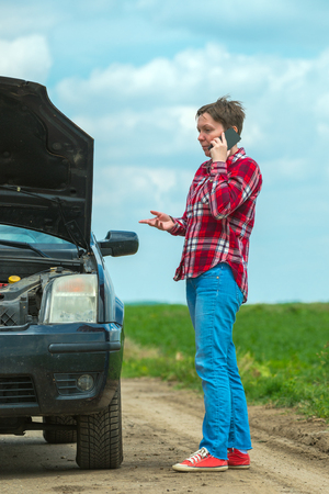 Unhappy frustrated female calling car mechanic repair shop with mobile phone from country dirt road