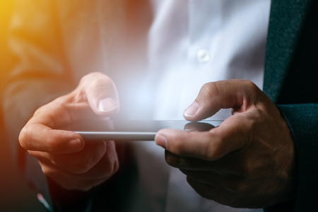 Businessman playing mobile app video game on smart phone, close up of male hands