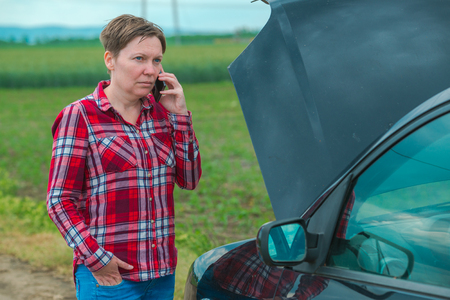 Adult caucasian woman standing by the broken car on country road and talking on mobile phone