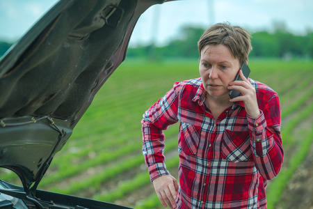Woman calling car repair service from country road, adult female person standing by the broken vehicle in countryside Stock Photo