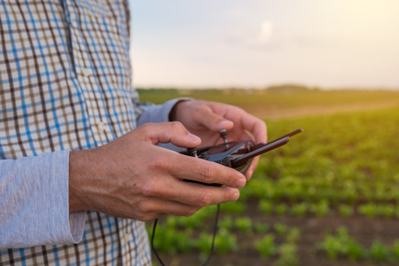 Hands of farmer using drone remote control, smart farming agricultural activity and teh future of agriculture
