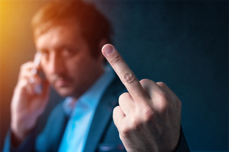 Rude businessman talking on mobile phone and giving middle finger gesture as sign of agreement refusal, job quitting or displeased reaction
