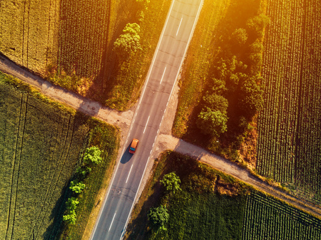 Aerial view of traffic on two lane road through countryside and cultivated fields Stock Photo