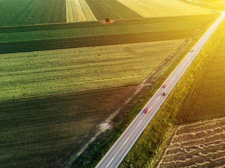 cultivating: Aerial view of traffic on two lane road through countryside and cultivated fields Stock Photo