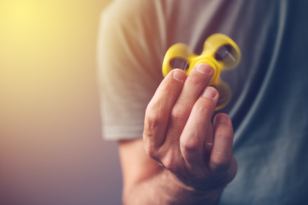 games hand: Adult man playing with fidget spinner toy, selective focus