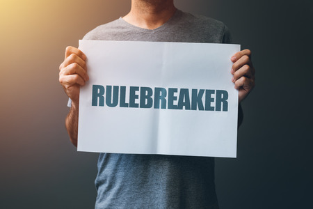 Rulebreaker attitude, person who breakes the rules concept with male holding poster