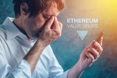 Ethereum cryptocurrency value drops concept with male businessman and smartphone