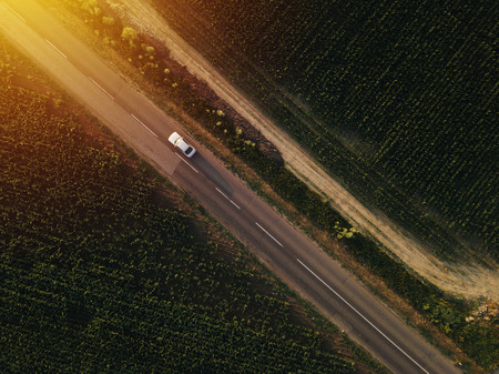 Aerial view of lonely car on the road driving towards sunset, drone point of view