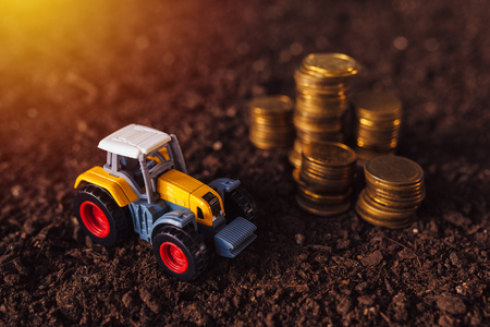 Agricultural tractor toy and golden coins on fertile soil land, income from activity in agriculture or investment and bank loans for farm development Stock fotó
