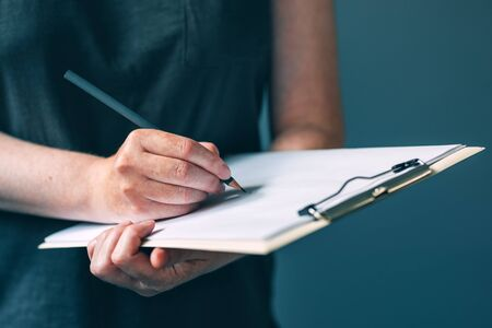 Casual adult female writing notes on notepad paper, unrecognizable woman with pencil, selective focus Stock Photo