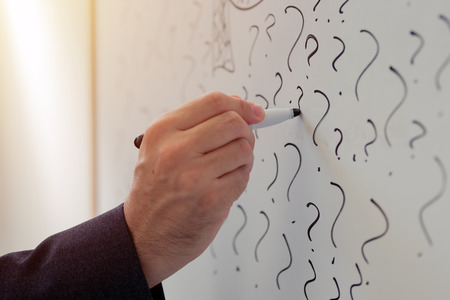 Businessman sketching many question marks on office whiteboard, uncertainty and unpredictability in business Stock Photo