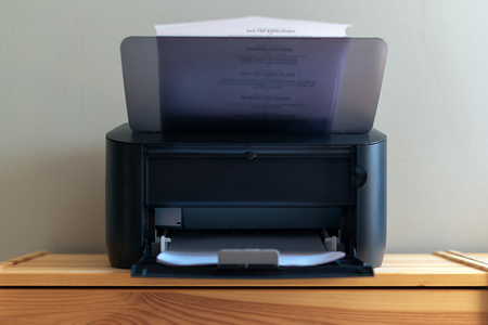Small office printer printing documents, selective focus