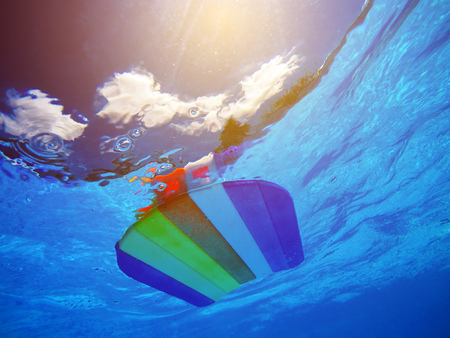 Rainbow pattern styrofoam swimming board or baseboard floating in swimming pool water, summertime vacation recreational activity object in the poolside, underwater view