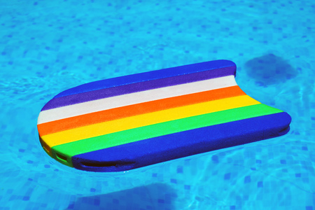 Rainbow pattern styrofoam swimming board or baseboard floating in swimming pool water, summertime vacation recreational activity object in the poolside