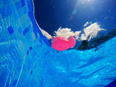Generic rubber fish toy floating in swimming pool, summertime activity and enjoyment, underwater view