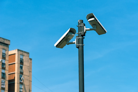 Surveillance cameras in urban district against blue sky Stock Photo
