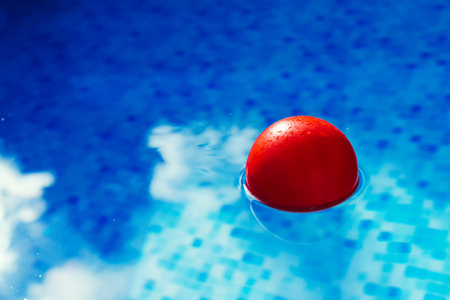 Red ball floating in clear blue swimming pool water, plaything in poolside for summertime activity and recreation Stock Photo