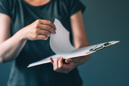 Casual adult female reading notes from notepad paper, unrecognizable woman note pad, selective focus Stock Photo