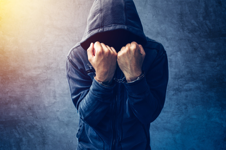 Arrested computer hacker and cyber criminal with handcuffs wearing hooded jacket hiding face Stock Photo