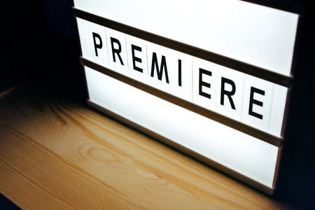 Vintage illuminated lightbox Premiere sign in cinema movie or for radio and television live audience broadcast Stock Photo