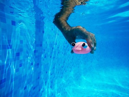 スイミング プール、夏季のアクティビティと楽しみ、水中撮影での一般的なゴムの魚おもちゃで遊ぶ男