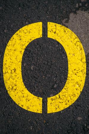 Letter O on asphalt road, top view