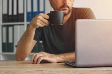 Freelancer drinking coffee and looking at laptop screen in home office interior