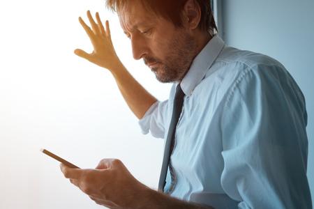 オフィスの窓の横に立ってスマートフォンを使うビジネスマン。SMS メッセージまたはモバイル アプリを通るビジネスコミュニケーション。ビジネス