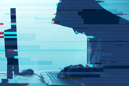 Hooded computer hacker working on desktop PC computer. P2P and piracy, computer virus and trojans, phishing, malware and ransomware concept with glitch effect. 스톡 콘텐츠