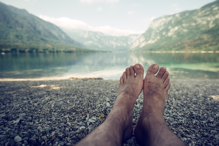 bohinj: Summer holiday by the lake, barefoot adult caucasian male relaxing on beach pebbles and looking into water and mountains in the distance. Enjoying vacation and nature beauty.