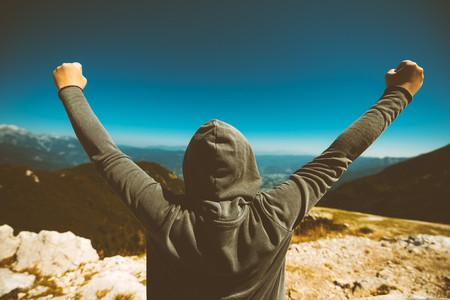 Achievement and triumph. Victorious female person standing on mountain top with arms raised in V. Achievement and accomplishment in life. Toned image. Stock Photo