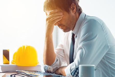 Architekt und Bauingenieur, die Probleme bei der Arbeit im Büro haben, Bauingenieur, der mit Computer und Skizzen auf einem Bauprojekt, selektiver Fokus arbeitet