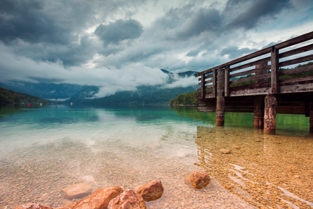 Wooden pier at beautiful Bohinj lake landscape on cloudy autumn day. Unique glacial lake in Slovenian national park Triglav. Stock Photo