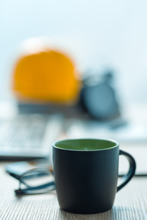 Coffee break in architecture and interior design studio, black cup of hot drink on office desk