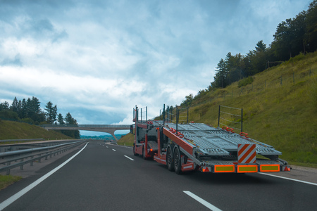 Semi truck with empty car carrier trailer on highway road Stock Photo