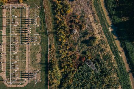 Vista aerea dell'impianto e dei piloni della sottostazione elettrica di elettricità nel campo, vista superiore dell'infrastruttura industriale dal pov di drone. Archivio Fotografico - 89019952