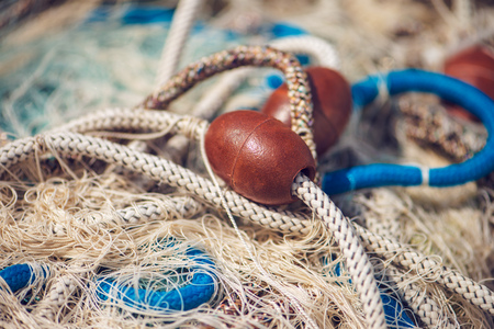 Pile of commercial fishing net with cords and floats as abstract background, selective focus