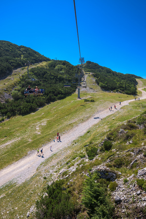 VOGEL MOUNTAIN, SLOVENIA - AUGUST 30, 2017: Aerial view of unidentifiable group of mountain hikers walking along footpath in popular travel destination for outdoor sports. Editorial