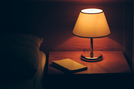 Vintage lamp on night table in hotel room. Retro styled bedroom interior. Stockfoto